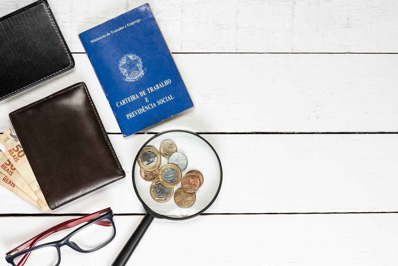 work permit, wallet, Brazilian money, Brazilian coins, magnifying glasses, glasses, leather notepad, white background, space for text, pinus background, objects on the left, top view